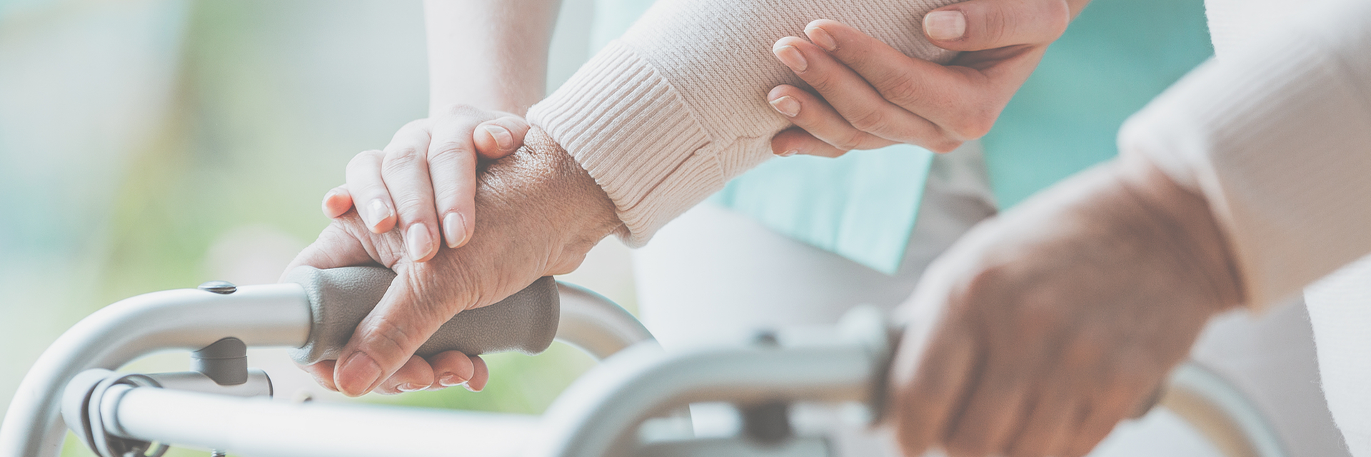 close up image of nurses hand assisting patient's hand on walker