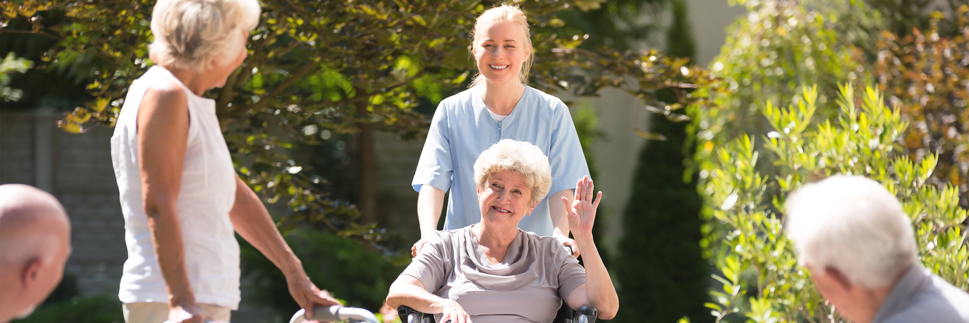 patient waving while nurse pushes her in a wheelchair